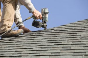 Man working on roof with nail gun. Waynesboro Roofing 540-655-1718